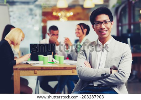 Portrait of cheerful businessman with arms folded sitting in front of colleagues - stock photo