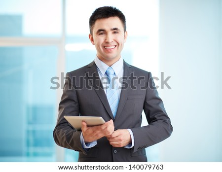 Portrait of cheerful businessman with touchpad looking at camera - stock photo