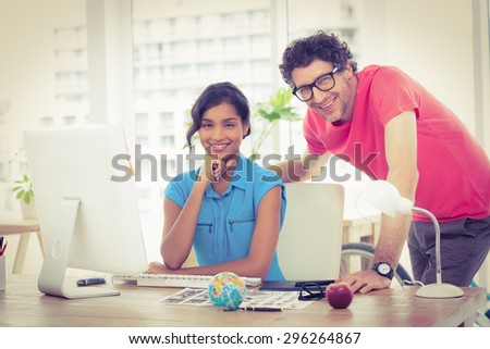 Portrait of cheerful colleagues using computer in the office - stock photo