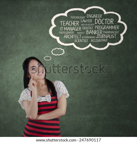 Portrait of cheerful college student thiking about her aspiration in the classroom - stock photo