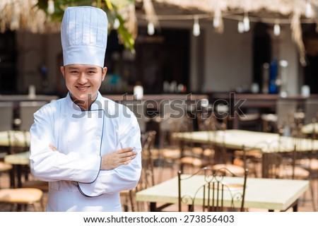 Portrait of cheerful confident cook standing in front of cafe - stock photo