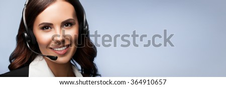 Portrait of cheerful customer support female phone operator in headset, over grey background. Consulting and assistance service call center. Copyspace area for slogan or text message. - stock photo