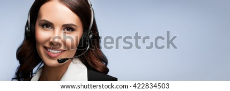 Portrait of cheerful customer support female phone operator in headset, with blank copyspace area for slogan or text, over grey background - stock photo