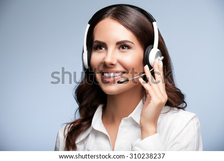 Portrait of cheerful customer support female phone worker, looking up, against grey background. Consulting and assistance service call center. - stock photo