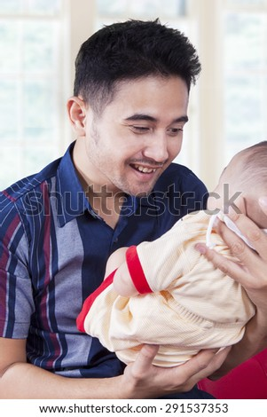 Portrait of cheerful daddy, holding his male baby and smiling on the baby at home - stock photo