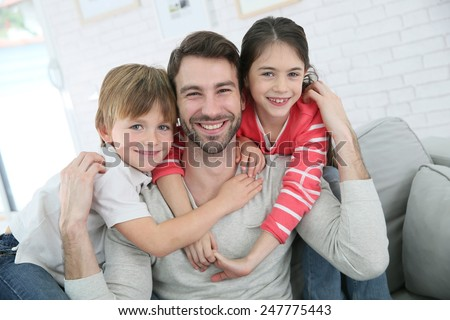 Portrait of cheerful daddy with kids - stock photo