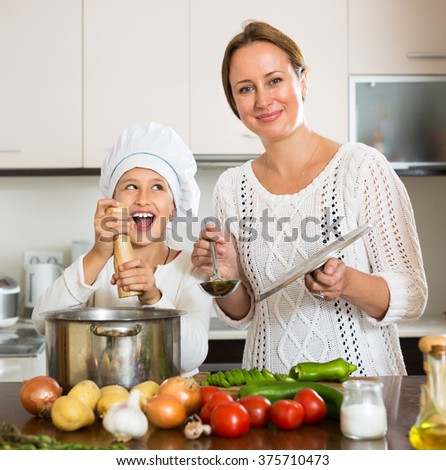 Portrait of cheerful daughter and smiling mom with vegetables and casserole in kitchen at home - stock photo