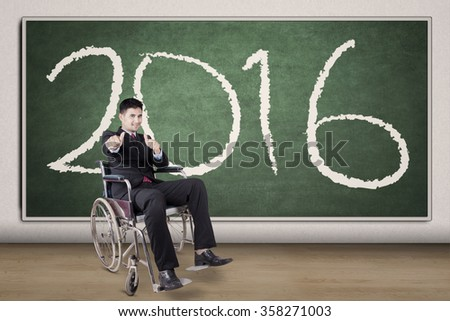 Portrait of cheerful disabled businessman showing thumbs up while sitting on wheelchair with numbers 2016 on blackboard - stock photo