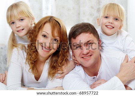 Portrait of cheerful family in white clothes looking at camera - stock photo