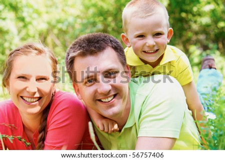 Portrait of cheerful family on summer vacation resting in park - stock photo