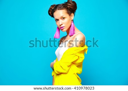 portrait of cheerful fashion hipster girl in casual colorful vivid hipster yellow summer clothes on blue background - stock photo