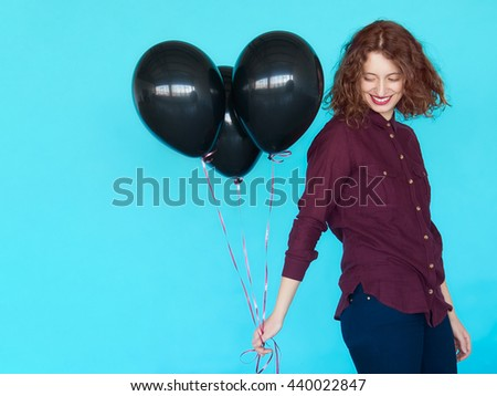 Portrait of cheerful fashion hipster girl with caucasian appearance, standing over blue color wall and holding a bunch of black balloons - stock photo