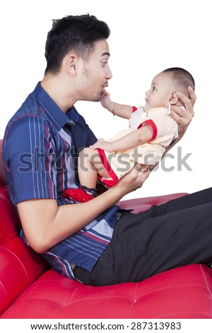 Portrait of cheerful father holding and playing with his baby boy on the sofa, isolated on white - stock photo