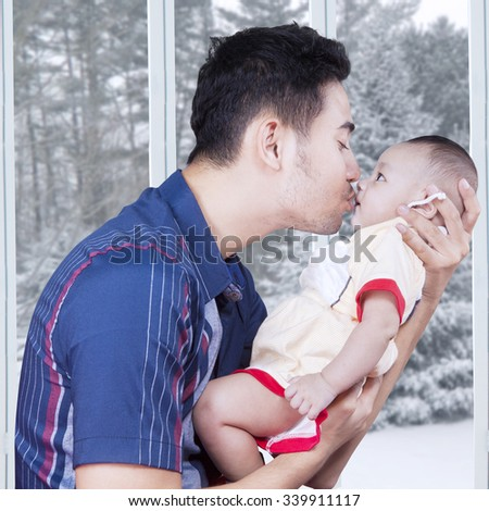 Portrait of cheerful father holding his male baby at home and kissing the baby, shot with winter background on the window - stock photo