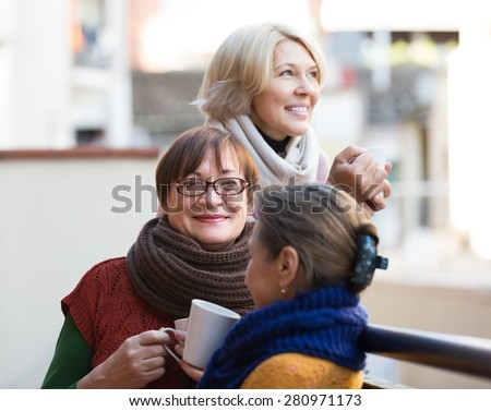 Portrait of cheerful female pensioner friends drinking coffee at patio. Focus on brunette - stock photo