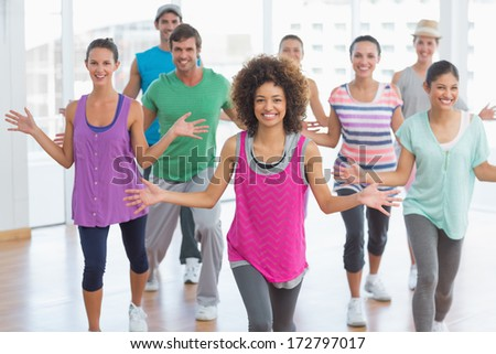 Portrait of cheerful fitness class and instructor doing pilates exercise in bright room - stock photo