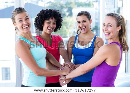 Portrait of cheerful friends holding hands while standing at fitness studio - stock photo