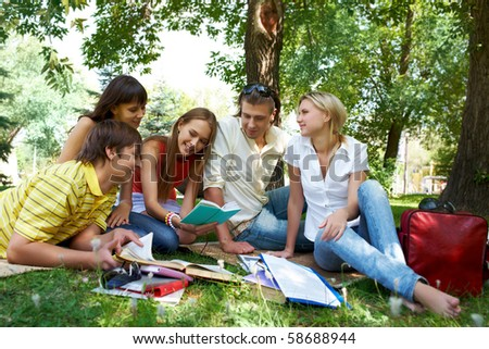 Portrait of cheerful friends listening to pretty girl while she reading outdoors - stock photo