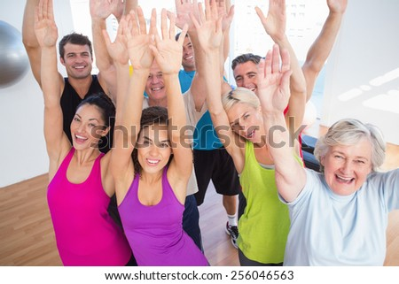 Portrait of cheerful friends with hands raised at fitness studio - stock photo