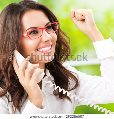 Portrait of cheerful gesturing brunette businesswoman or support phone worker, at office - stock photo