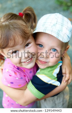 Portrait of  cheerful girl and boy hugging fun in outdoor - stock photo