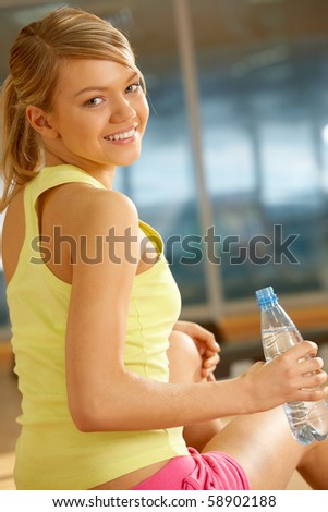 Portrait of cheerful girl holding bottle of water in hand and smiling at camera - stock photo
