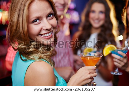 Portrait of cheerful girl holding cocktail in martini glass and looking at camera on background of her friends at party - stock photo
