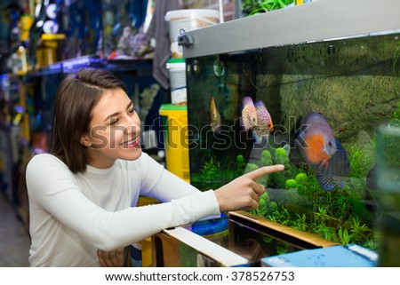 Portrait of cheerful girl watching tropical fish  - stock photo