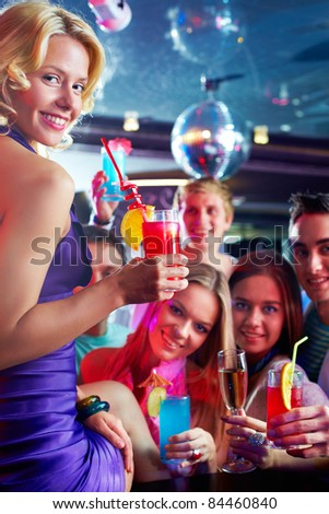 Portrait of cheerful girl with cocktail looking at camera with friends on background - stock photo
