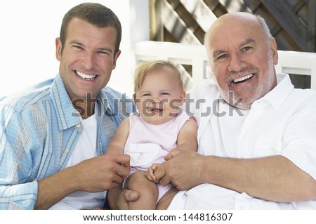 Portrait of cheerful grandfather with father and daughter - stock photo