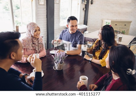 portrait of Cheerful group of friends having a conversation at the cafe - stock photo