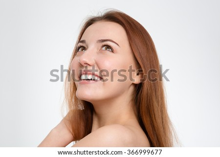 Portrait of cheerful happy young woman with long brown hair looking up over white background - stock photo