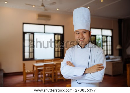 Portrait of cheerful head chef in Asian restaurant - stock photo