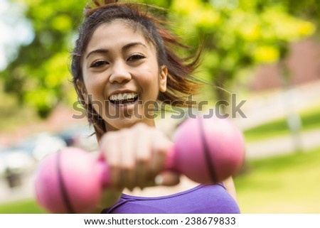 Portrait of cheerful healthy young woman lifting dumbbell in park - stock photo