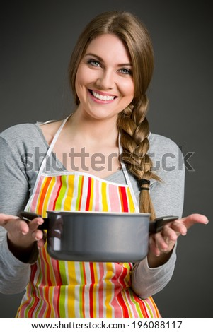Portrait of cheerful housewife in apron holding saucepan - stock photo