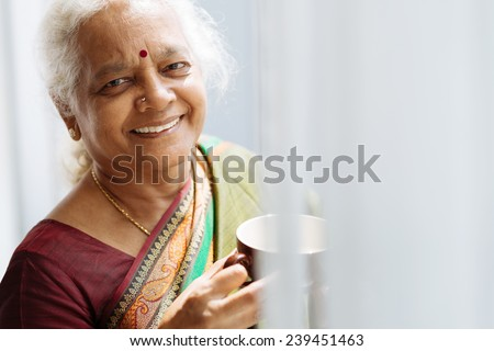 Portrait of cheerful Indian woman with a mug standing by the window - stock photo