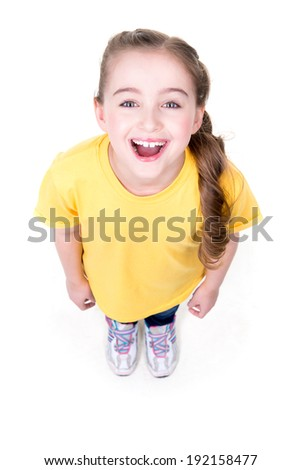 Portrait of cheerful little girl looking up in yellow t-shirt. Top view. Isolated on white background. - stock photo