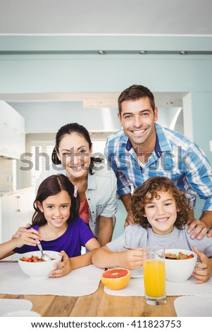 Portrait of cheerful man and woman with children having breakfast at home - stock photo