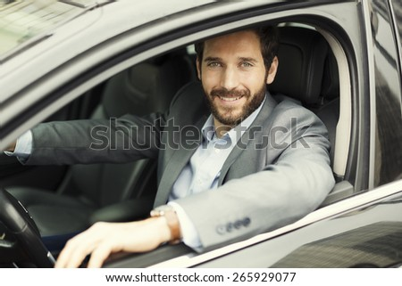 Portrait of cheerful man in his car. looking camera - stock photo