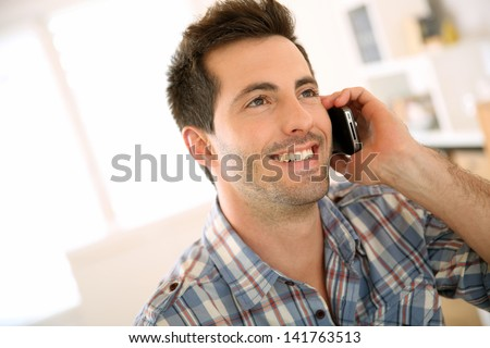 Portrait of cheerful man talking on the phone - stock photo