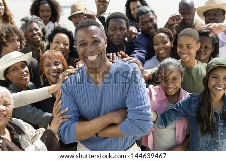 Portrait of cheerful mature man surrounded by people - stock photo