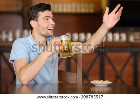 Portrait of cheerful men drinking beer at the bar and appeal to the waiter - stock photo
