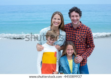Portrait of cheerful parents with children standing on shore at beach - stock photo