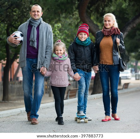 Portrait of cheerful parents with two smiling children spending time together outdoors - stock photo