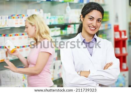 portrait of cheerful pharmacist chemist woman in pharmacy drugstore - stock photo