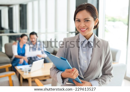 Portrait of cheerful real estate agent with a clipboard - stock photo