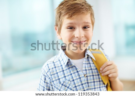 Portrait of cheerful schoolboy with backpack looking at camera - stock photo
