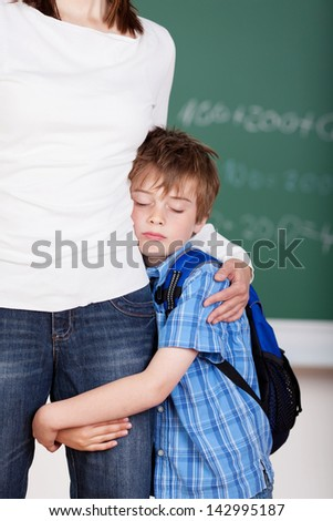 Portrait of cheerful schoolchild hugs his mother after school - stock photo