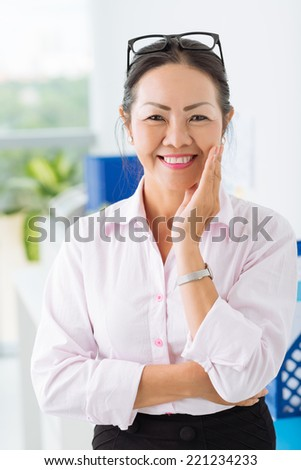 Portrait of cheerful senior businesswoman looking at the camera - stock photo