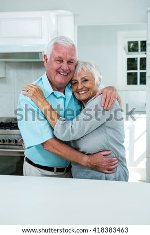 Portrait of cheerful senior couple hugging in kitchen at home - stock photo
